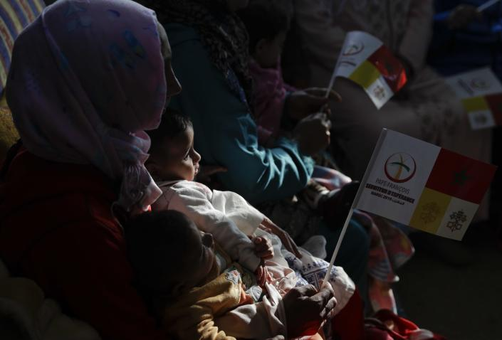 A woman holds her child as they wait for Pope Francis to arrive at the Rural Center for Social Services at Temara, south of Rabat, Morocco, Sunday, March 31, 2019. Pope Francis is in Morocco for a two-day trip aimed at highlighting the North African nation's Christian-Muslim ties, while also showing solidarity with migrants at Europe's door and tending to a tiny Catholic flock. (AP Photo/Gregorio Borgia)