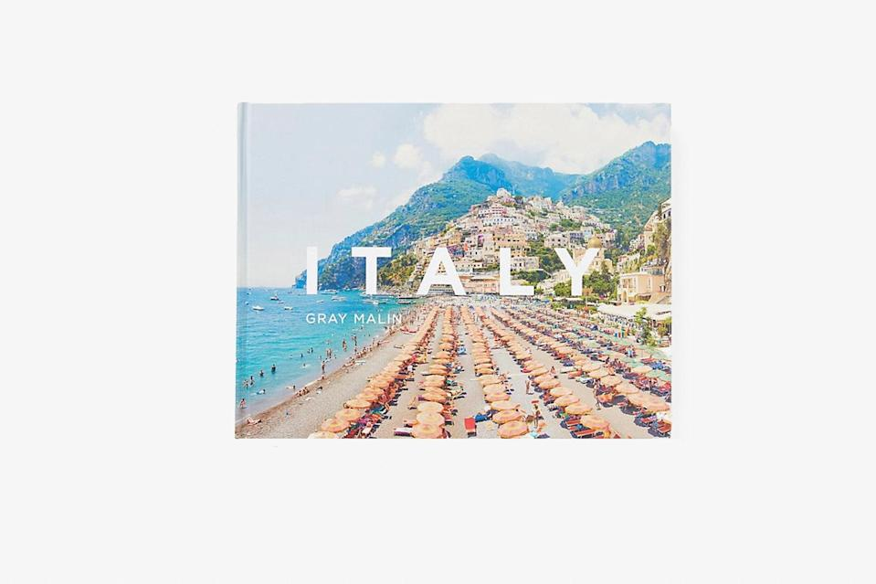 """Aerial shots, pleasingly neat geometric patterns in the form of pinwheel-like umbrellas, and brilliant blue hues: You know Gray Malin when you see him. In <em>Italy</em>, the king of aesthetics showcases the photographs he took during summer visits to <a href=""""https://www.cntraveler.com/package/secret-italy?mbid=synd_yahoo_rss"""" rel=""""nofollow noopener"""" target=""""_blank"""" data-ylk=""""slk:the coast"""" class=""""link rapid-noclick-resp"""">the coast</a>. The pictured regions are scattered along the border of the boot—the Amalfi Coast, Capri, Cinque Terre, Lake Como, Puglia, Sicily, <a href=""""https://www.cntraveler.com/story/a-guide-to-tuscan-wine-country?mbid=synd_yahoo_rss"""" rel=""""nofollow noopener"""" target=""""_blank"""" data-ylk=""""slk:Tuscany"""" class=""""link rapid-noclick-resp"""">Tuscany</a>, and Portofino grace the glossy pages of this cheerful <a href=""""https://www.cntraveler.com/story/the-coffee-table-books-to-give-and-keep-this-year?mbid=synd_yahoo_rss"""" rel=""""nofollow noopener"""" target=""""_blank"""" data-ylk=""""slk:coffee table book"""" class=""""link rapid-noclick-resp"""">coffee table book</a>. Sunbathers on the hot white rocks of Grotta della Poesia, boats bobbing in the azure waters of Portofino harbor, and sun-bleached clouds above the seaside cliffs of Capri will give your imagination all it needs to make it through winter. In the introduction, Malin even likens Italy to an ice cream cone in July. Whether or not you find that analogy silly, the bright and beachy images that follow are certainly as enticing as it gets. $40, Anthropologie. <a href=""""https://www.anthropologie.com/shop/italy"""" rel=""""nofollow noopener"""" target=""""_blank"""" data-ylk=""""slk:Get it now!"""" class=""""link rapid-noclick-resp"""">Get it now!</a>"""