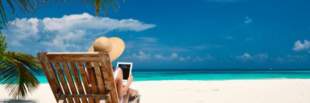 Young woman with e-reader on the beach.