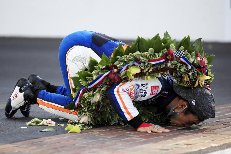 Takuma Sato celebrates by kissing the bricks after winning.