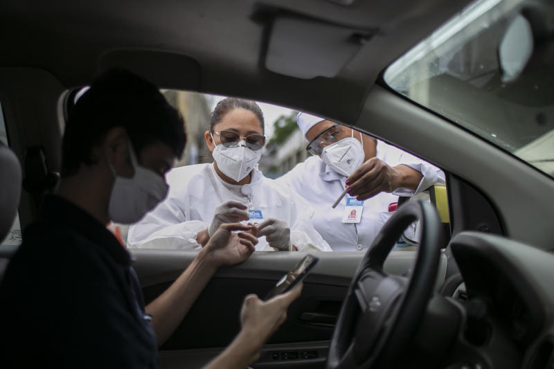RIO DE JANEIRO, BRAZIL - JUNE 15: Health workers perform a test of coronavirus (COVID-19) to a taxi driver through a drive-thru system at the Marques de Sapucai Sambadrome on June 15, 2020 in Rio de Janeiro, Brazil. The municipality of Rio de Janeiro is testing taxi drivers with the most chance of exposing themselves to the virus, and the order will be defined according to the number of runs made through the TaxiRio (a taxi ride app from the city of Rio de Janeiro) application. With the drive-thru system, the taxi driver will not have the need to disembark from the vehicle to collect material, and the test result will be sent via a text message on the cell phone. The city expects to complete the testing of 5,000 taxi drivers in ten days. (Photo by Bruna Prado/Getty Images)