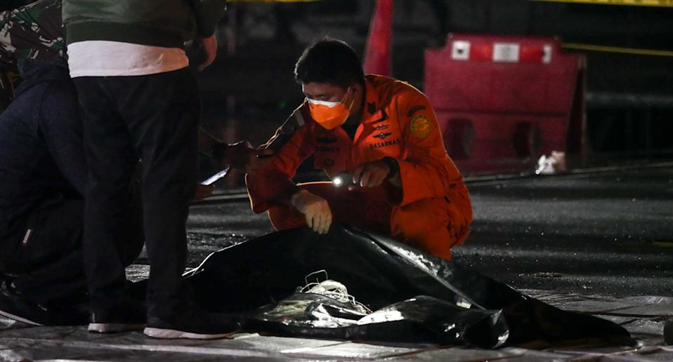 JAKARTA, INDONESIA - JANUARY 10: Officers from Sriwijaya Air and The National Search and Rescue Agency of Indonesia (BASARNAS) check a fragment of Indonesian Sriwijaya Air Flight 182 Boeing 737 crashed into the Java Sea on Saturday at Tanjung Priok Port in Jakarta, Indonesia on January 10, 2021.