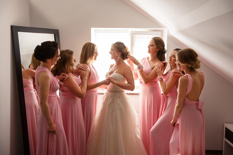 A woman in a wedding dress with her bridesmaids wearing pink
