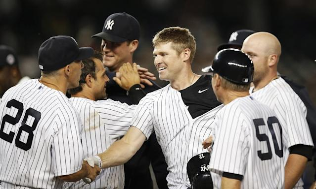 New York Yankees manager Joe Girardi (28) congratulates newly acquired New York Yankees Chase Headley, center, who hit a 14th inning, game-wimnning, walk-off RBI single to lift the Yankees to a 2-1 victory over the Texas Rangers in a baseball game at Yankee Stadium in New York, Wednesday, July 23, 2014. (AP Photo)