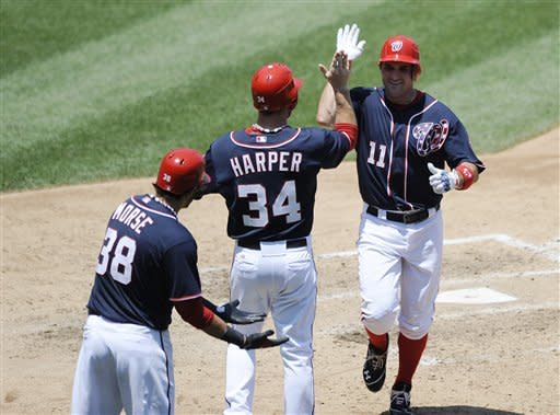 Washington Nationals' Ryan Zimmerman (11) celebrates his two-run home run with Bryce Harper (34) and Michael Morse (38) against the San Francisco Giants during the fifth inning of a baseball game, Wednesday, July 4, 2012, in Washington. The Nationals won 9-4. (AP Photo/Nick Wass)