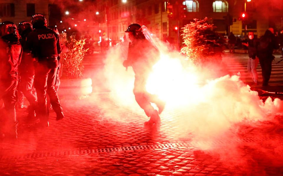 Flares explode as police clash with activists during a protest called by Forza Nuova far-right group against the government restriction measures to curb the spread of Covid in Rome on Friday - LaPresse