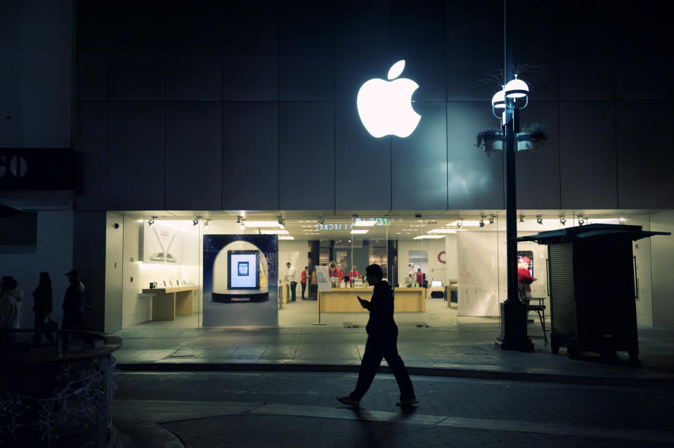 Silhouette of man looking at his phone while walking by the Apple Store on the Third Street Promenade at night in Santa Monica