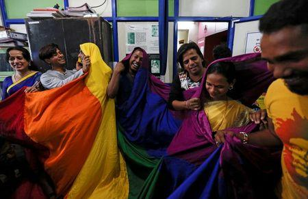 Gay rights activists cover themselves with a rainbow flag as they celebrate the Supreme court's decision on gay sex in Mumbai