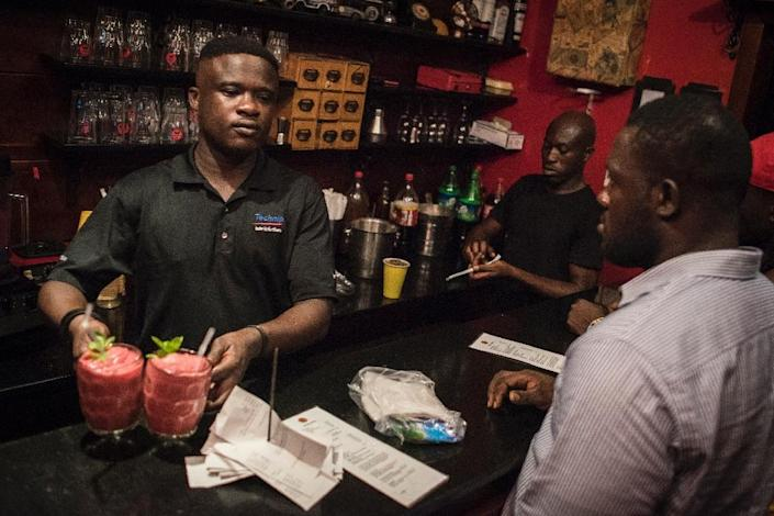 A barman at the Republic Bar & Grill in Accra serves a Kokroko cocktail, a drink made of Sobolo and Akpeteshie (AFP Photo/CRISTINA ALDEHUELA)