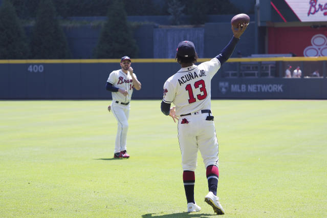 Braves star Ronald Acuña Jr. tossed a football around prior to a 2019 game. Baseball's scheduling model may need to evolve to keep it in front of fans with other sports competing. (Photo by David John Griffin/Icon Sportswire via Getty Images)