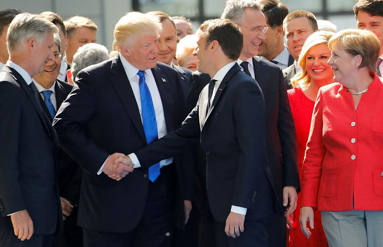 <p>President Donald Trump jokes with French President Emmanuel Macron about their handshakes in front of NATO leaders, including German Chancellor Angela Merkel, NATO Secretary General Jens Stoltenberg (2ndR) and Belgium King Philippe (L), at the start of the NATO summit at their new headquarters in Brussels, Belgium, May 25, 2017. (Photo: Jonathan Ernst/Reuters) </p>
