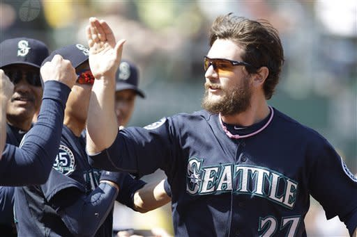 Seattle Mariners' John Jaso, right, is congratulated after scoring against the Oakland Athletics in the second inning of a baseball game Saturday, Sept. 29, 2012, in Oakland, Calif. Jaso scored on a double throwing error by the Athletics. (AP Photo/Ben Margot)
