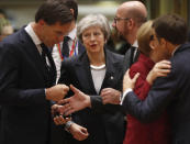 FILE - In this Thursday, Dec. 13, 2018 file photo British Prime Minister Theresa May, center, arrives for a round table meeting at an EU summit in Brussels. Britain and the European Union have struck a provisional free-trade agreement that should avert New Year's chaos for cross-border commerce and bring a measure of certainty to businesses after years of Brexit turmoil. The breakthrough on Thursday, Dec. 24, 2020 came after months of tense and often testy negotiations that whittled differences down to three key issues: fair-competition rules, mechanisms for resolving future disputes and fishing rights. (AP Photo/Alastair Grant, File)