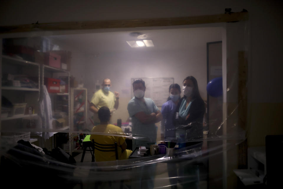 FILE - In this July 14, 2020 file photo, health care providers gather inside a work area protected by a sheet of plastic at the Eurnekian Ezeiza Hospital on the outskirts of Buenos Aires, Argentina, during a government-ordered lockdown to curb the spread of the new coronavirus. Argentina reached 1 million confirmed coronavirus cases on Monday, Oct. 19, 2020, according to the Ministry of Health. (AP Photo/Natacha Pisarenko, File)