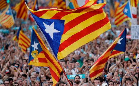 Protesters wave pro-independence Catalan Estelada flags during a demonstration in Barcelona - Credit: AFP