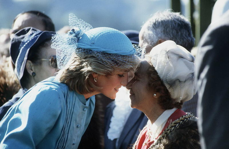Princess Diana rubbing noses — the traditional Maori greeting — with a Maori woman in New Zealand, wearing her turquoise silk suit. (Photo: Getty)