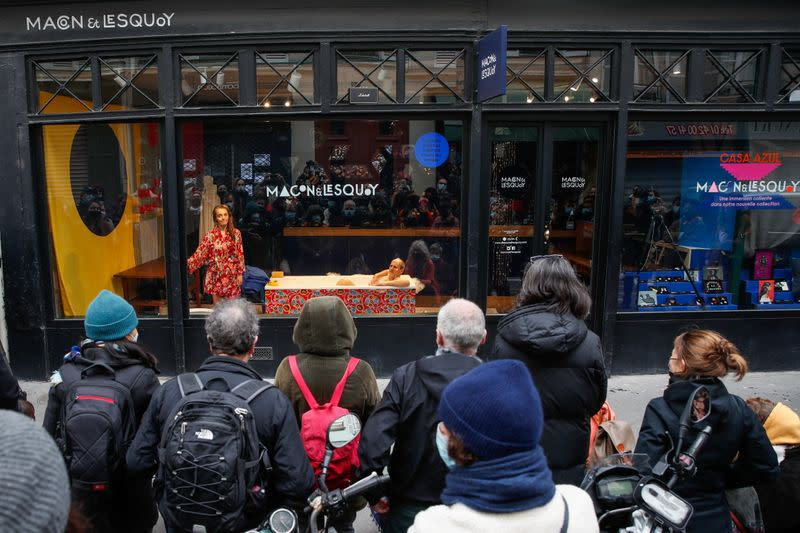 French actors perform a play behind store window in Paris