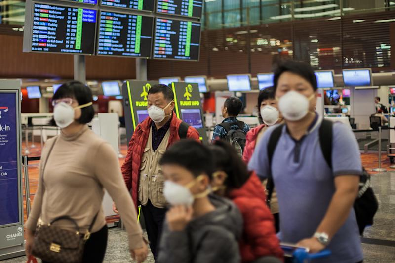 MRT, SINGAPORE - 2020/01/29: A family seen wearing protective n95 masks as they walk around Changi Airport in Singapore. Many people have started wearing protective masks in many places around the world due to the fear of Wuhan coronovirus outbreak. Ten people tested positive for the Wuhan coronavirus in Singapore as of 29th January 2020- as reported by the country's Ministry of Health (MOH). (Photo by Maverick Asio/SOPA Images/LightRocket via Getty Images)