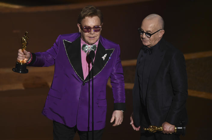 """Elton John, left, and Bernie Taupin accept the award for best original song for """"(I'm Gonna) Love Me Again"""" from """"Rocketman"""" at the Oscars on Sunday, Feb. 9, 2020, at the Dolby Theatre in Los Angeles. (AP Photo/Chris Pizzello)"""