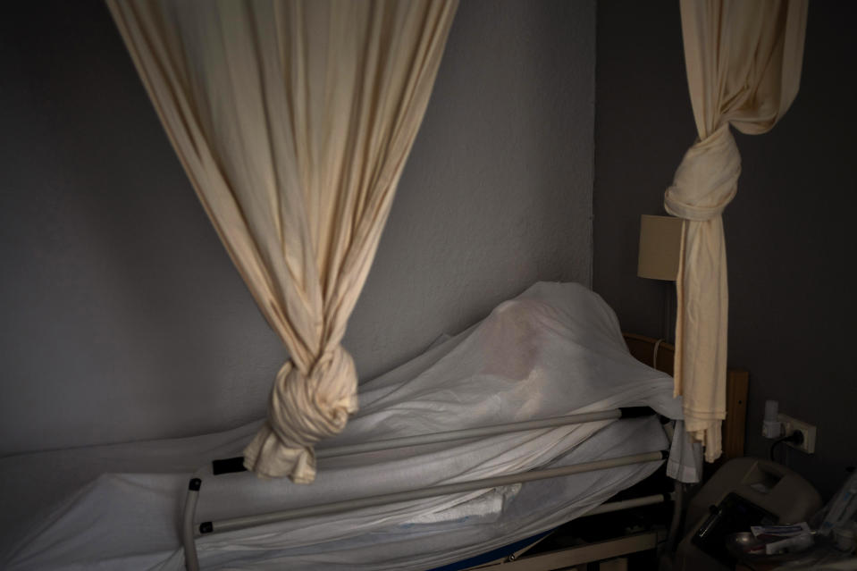 The body of an elderly person who died of COVID-19 is covered with a sheet on her bed in a nursing home in Barcelona, Spain, Friday, Nov. 13, 2020. (AP Photo/Emilio Morenatti)