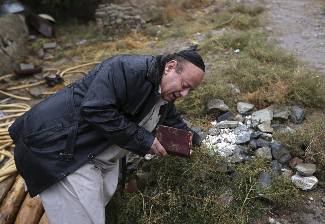 Zabulon Simantov, an Afghan Jew, prays at a Jewish cemetery in Kabul November 5, 2013. In his 50s, Simintov is the last known Afghan Jew to remain in the country. He has become something of a celebrity over the years and his rivalry with the next-to-last Jew, who died in 2005, inspired a play. Picture taken November 5, 2013. REUTERS/Omar Sobhani (AFGHANISTAN - Tags: SOCIETY RELIGION)
