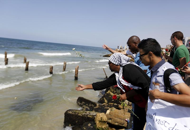 Palestinians throw roses into the Mediterranean Sea near Gaza City on September 18, 2014 to mourn those who drowned when a ship sank off Malta last week (AFP Photo/Mohammed Abed)