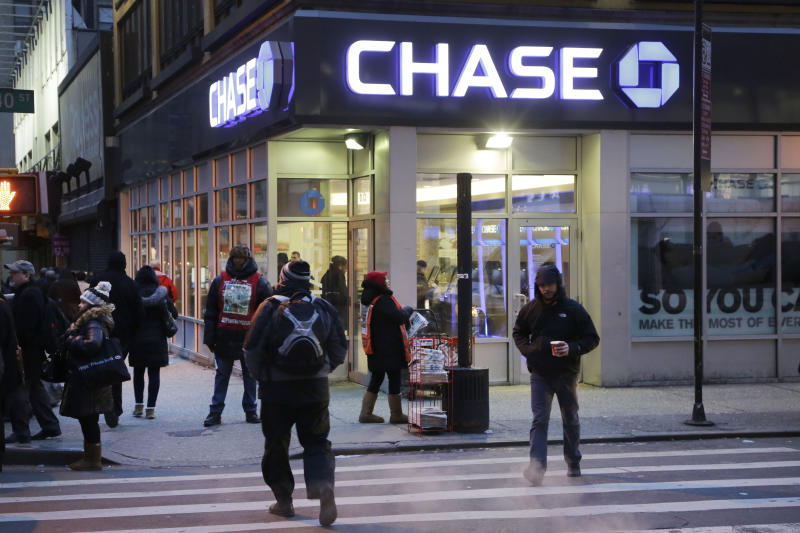People walk past a branch of Chase Bank, Wednesday, Jan. 14, 2015 in New York. JP Morgan Chase & Co. reports quarterly financial results Wednesday. JPMorgan Chase reported a 7 percent drop in fourth-quarter earnings Wednesday, hit by more legal costs and a drop in trading revenue. JPMorgan, the biggest U.S. bank by assets, said it earned $4.93 billion, or $1.19 a share, for the three-month period ending in December. (AP Photo/Mark Lennihan)