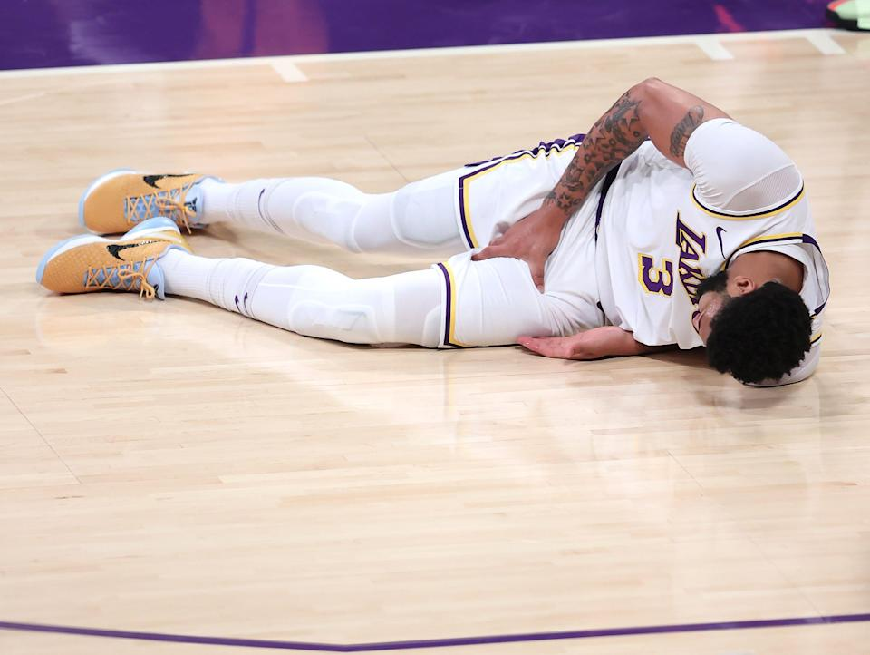 Anthony Davis #3 of the Los Angeles Lakers grabs his thigh after falling during the first half of Game Four of the Western Conference first-round playoff series against the Phoenix Suns at Staples Center on May 30, 2021 in Los Angeles, California.