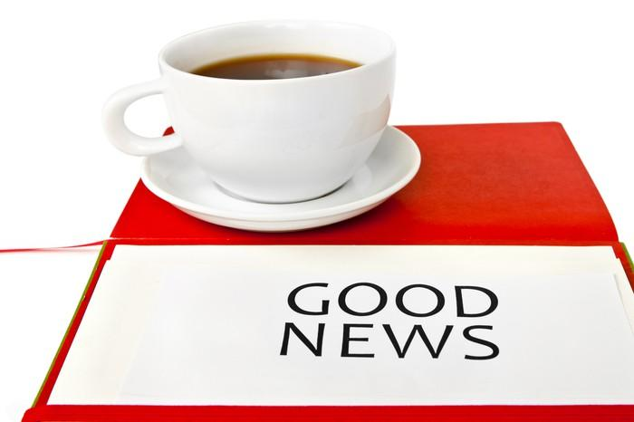 Cup of coffee and saucer on top of red paper with the words Good News printed on a white piece of paper.