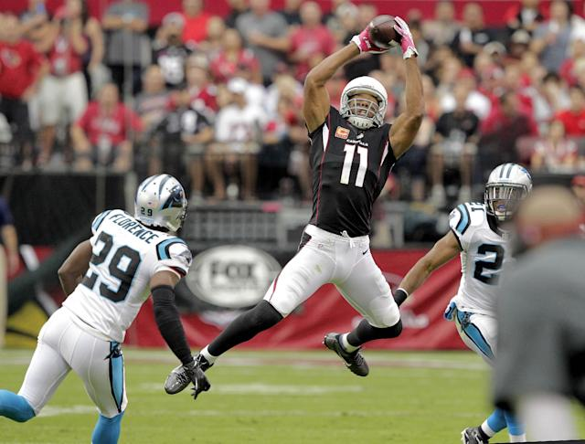 Arizona Cardinals wide receiver Larry Fitzgerald (11) pulls in a pass as Carolina Panthers cornerback Drayton Florence (29) and Mike Mitchell defends during the first half of a NFL football game, Sunday, Oct. 6, 2013, in Glendale, Ariz. (AP Photo/Rick Scuteri)