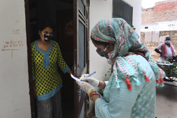 An Indian government school teacher writes down the details of a family during a survey at a residential neighborhood in New Delhi, India, Saturday, June 27, 2020. A massive survey to take down health details of New Delhi's entire population of 28 millions and test everyone with symptoms for COVID-19 started Saturday. Teams comprising of health workers and other government officials, including teachers went from home to home to conduct the survey, that is trying to screen everyone by July 6, as Delhi has become the worst hit city in India. (AP Photo/Manish Swarup)