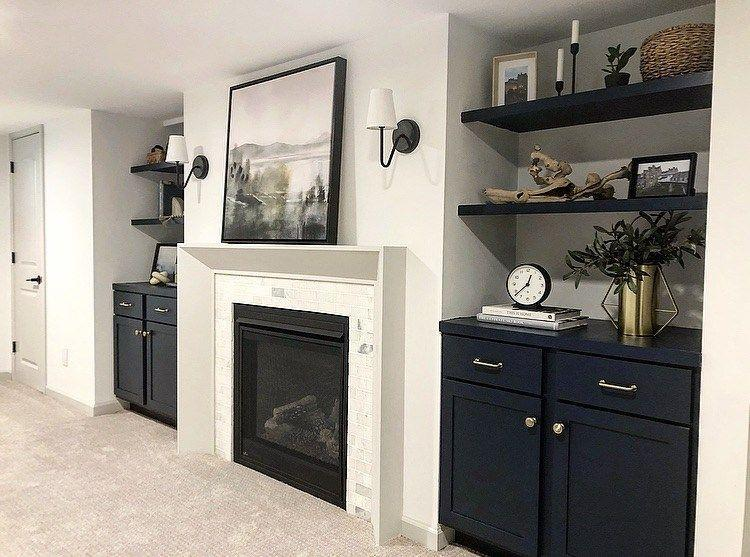"""<p>This bright, inviting space can be enjoyed year-round, thanks to cozy carpeting and a gas fireplace. Navy blue built-in cabinetry adds storage, and a beverage fridge means you'll never have to go far for refreshments!</p><p><strong>See more at <a href=""""https://simaspaces.com/our-1950s-basement-remodel-reveal-from-wood-paneled-to-white-and-bright/"""" rel=""""nofollow noopener"""" target=""""_blank"""" data-ylk=""""slk:Sima Spaces"""" class=""""link rapid-noclick-resp"""">Sima Spaces</a>. </strong></p><p><a class=""""link rapid-noclick-resp"""" href=""""https://go.redirectingat.com?id=74968X1596630&url=https%3A%2F%2Fwww.walmart.com%2Fip%2FFrigidaire-18-Can-4-Bottle-Retro-Beverage-Fridge-Temperature-Control-Stainless-EFMIS567-WM%2F934384277&sref=https%3A%2F%2Fwww.redbookmag.com%2Fhome%2Fg36061437%2Fbasement-ideas%2F"""" rel=""""nofollow noopener"""" target=""""_blank"""" data-ylk=""""slk:SHOP BEVERAGE FRIDGES"""">SHOP BEVERAGE FRIDGES</a></p>"""