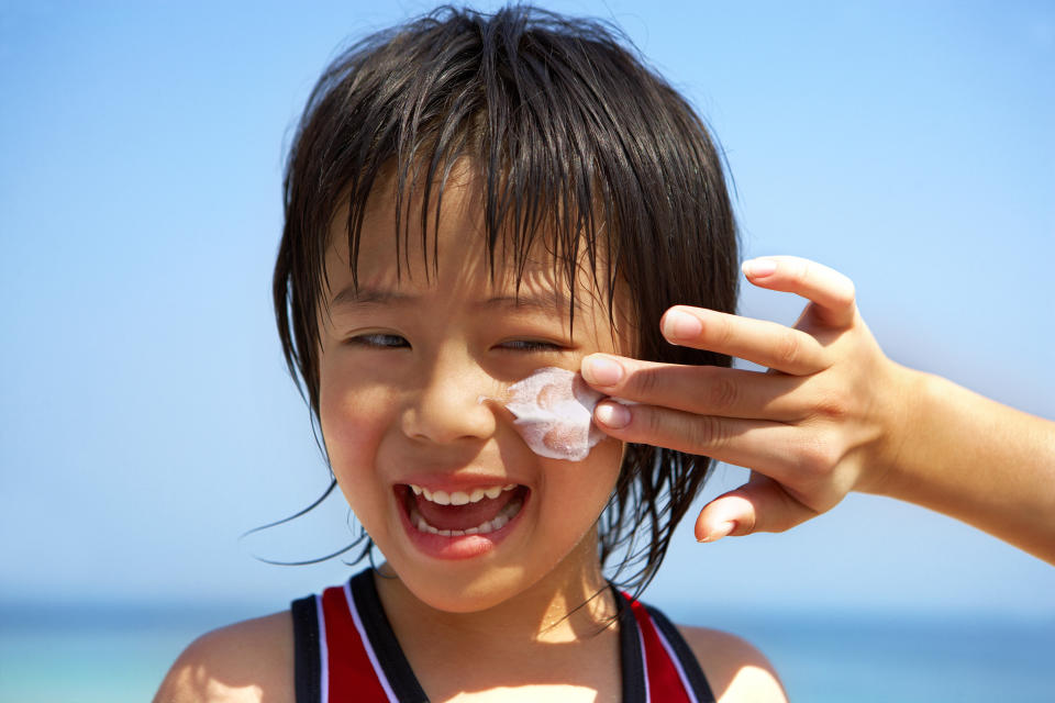 Young Asian boy at the beach having sunscreen applied to his face