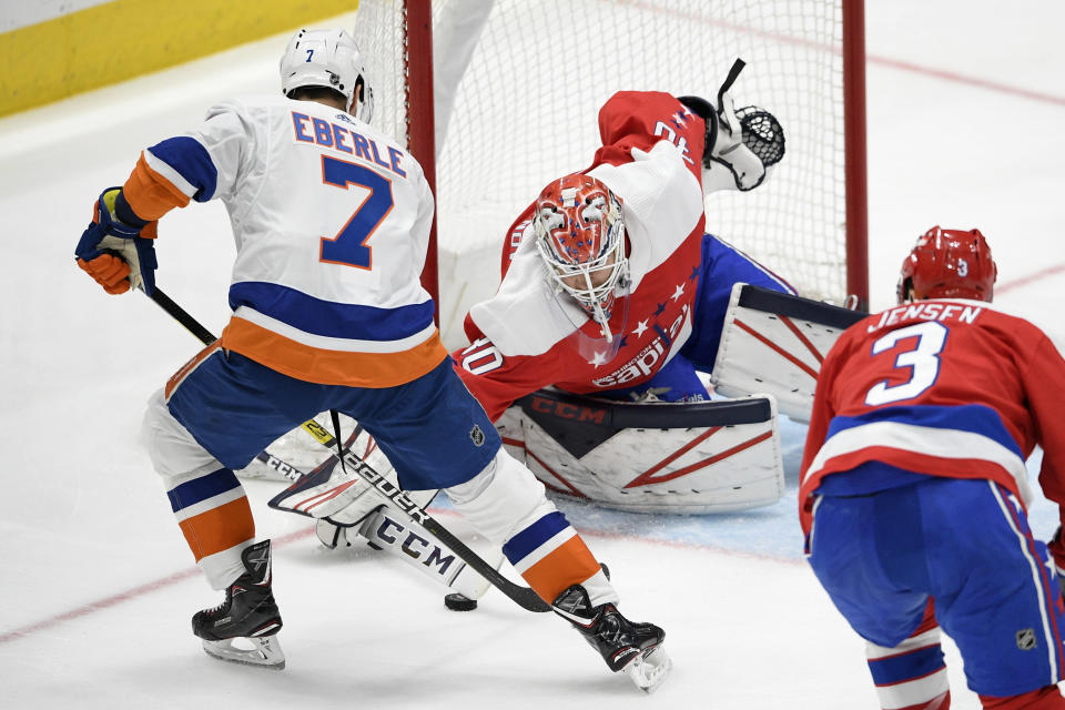 Washington Capitals goaltender Ilya Samsonov (30), of Russia, and New York Islanders right wing Jordan Eberle (7) battle for the puck during the second period of an NHL hockey game, Monday, Feb. 10, 2020, in Washington. (AP Photo/Nick Wass)