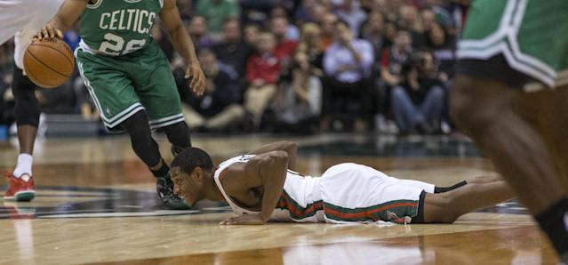Milwaukee Bucks' Brandon Knight falls to the floor as Boston Celtics' Phil Pressey dribbles past him during the first half of an NBA basketball game Saturday, Nov. 30, 2013, in Milwaukee. (AP Photo/Tom Lynn)