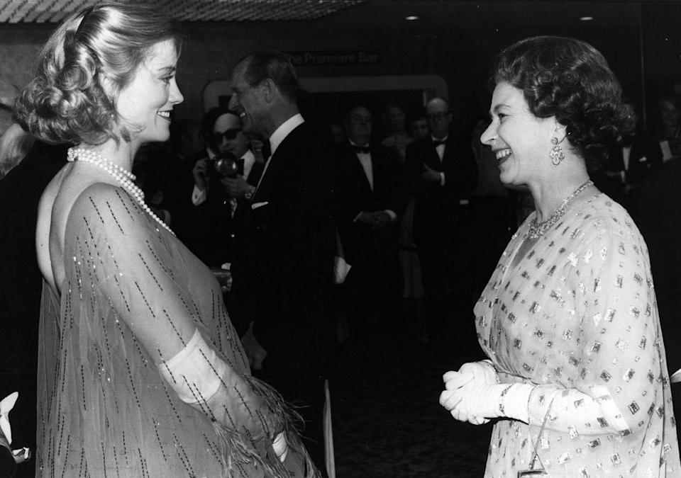 <p>Actress Cybill Shepherd was pregnant when she met the Queen at the premiere of <em>The Lady Vanishes</em> in 1979, but that didn't hold her back. Her fancy meet-the-Queen look: A sheer beaded and feathered caftan dress.</p>