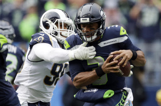 FILE - In this Oct. 7, 2018, file photo, Seattle Seahawks quarterback Russell Wilson, right, is sacked by Los Angeles Rams defensive tackle Aaron Donald, left, during the first half of an NFL football game, Sunday, in Seattle. With the second-place Seahawks visiting the Coliseum on Sunday for a rematch, the Rams have a chance to essentially end the division race with seven weeks to go. (AP Photo/Scott Eklund, File)