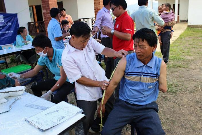 Yhong Vueyha (R) being measured for a prosthetic arm by a COPE (Cooperative Orthotic and Prosthetic Enterprise) employee at a mobile clinic in Xieng Khoang, Laos on June 2, 2016 (AFP Photo/Coraline Molinie)