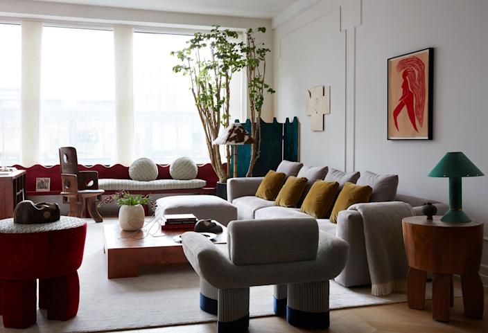 Valle's Smile chair (foreground) was inspired in part by the Ethiopian chief chair near the windows; Schumacher window panel fabric. An artwork by Jayson Musson hangs above the custom sofa, with its Holland & Sherry fabric, and a vintage coffee table by Milo Baughman; wool rug from Stark. A Ron Rezek lamp sits on the 1950s French butcher-block side table. Valle designed the folding screen and the window seat; its cushions are covered in the same Le Manach fabric that is used on the top of Valle's velvet side table.