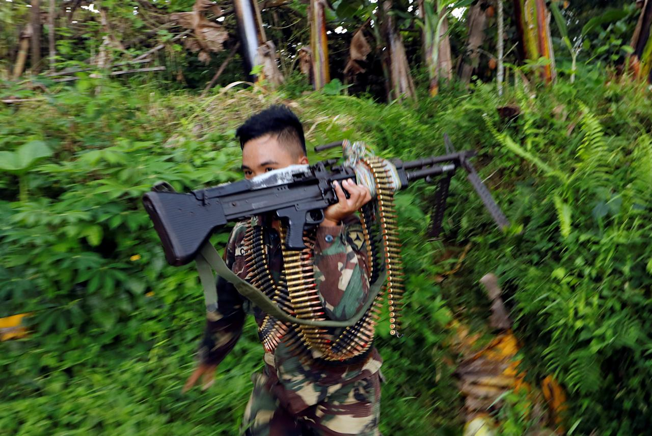 A Philippines army soldier runs with a machine gun to change the position to custody a truck with bodies of casualties retrieved from the fighting zone in Marawi city, Philippines June 28, 2017. REUTERS/Jorge Silva TPX IMAGES OF THE DAY
