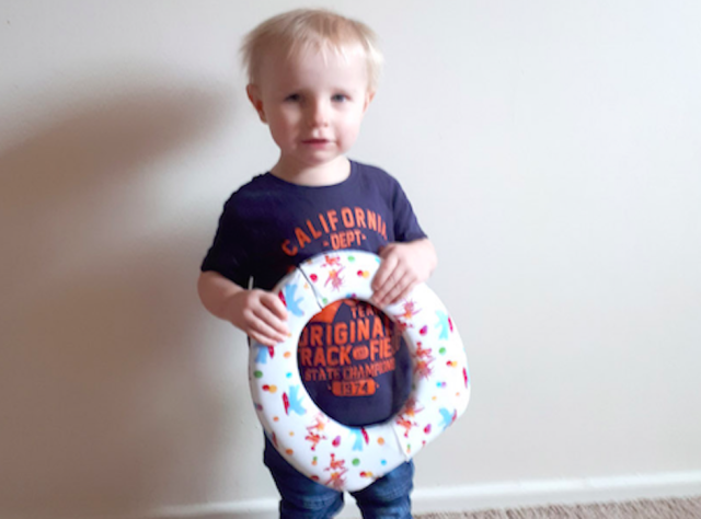 Two-year-old Flynn Edwards with the toilet seat that led the fire brigade to his door. (Caters)