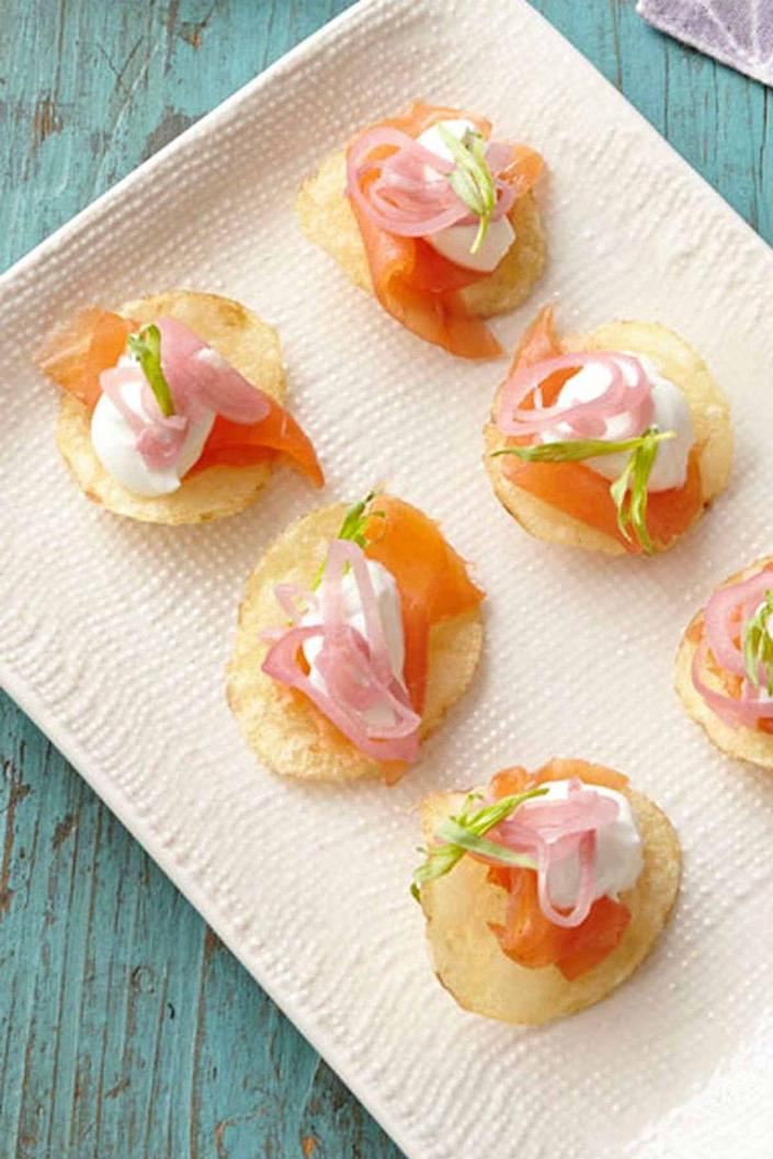 """<p>Potato chips are the base for this fancy-but-not-too-fancy recipe.</p><p><em><strong><a href=""""https://www.womansday.com/food-recipes/food-drinks/recipes/a39877/smoked-salmon-bites-recipe-ghk0414/"""" rel=""""nofollow noopener"""" target=""""_blank"""" data-ylk=""""slk:Get the Smoked Salmon Bites recipe."""" class=""""link rapid-noclick-resp"""">Get the Smoked Salmon Bites recipe.</a></strong></em></p>"""