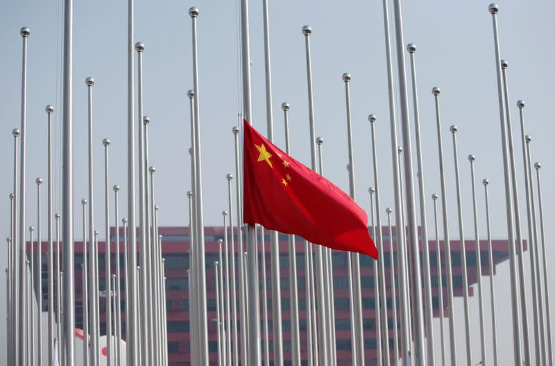 FILE PHOTO: The Chinese flag is raised in front of the China Pavilion during a flag raising ceremony at the Shanghai World Expo site in Shanghai