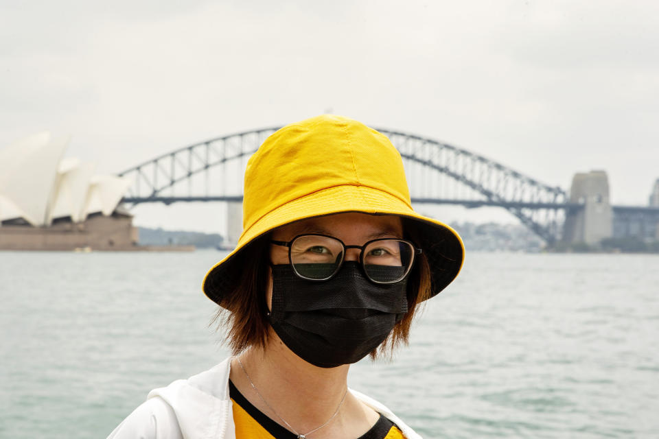 A tourist from Hong Kong is seen wearing a mask at Mrs Macquarie's Chair with the Sydney Harbour Bridge in the background.