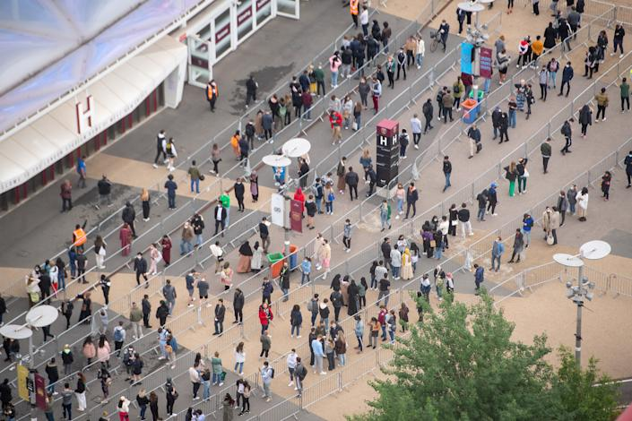 People queue outside an NHS Vaccination Clinic at West Ham's London Stadium in Stratford, east London. The NHS is braced for high demand as anyone in England over the age of 18 can now book a Covid-19 vaccination jab. Picture date: Saturday June 19, 2021.