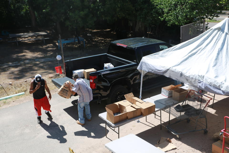 Volunteers load food donations into the truck of Gerald Ortiz Thursday, Sept. 23, 2021, in Chimayó, New Mexico. Ortiz said he regretted buying the truck a few months before the pandemic, and getting laid off from the company where he worked for 20 years. Half of Ortiz' unemployment, about $600 per month, has gone to his truck payments. To pay his bills he's cut back to eating only one meal per day.(AP Photo/Cedar Attanasio)