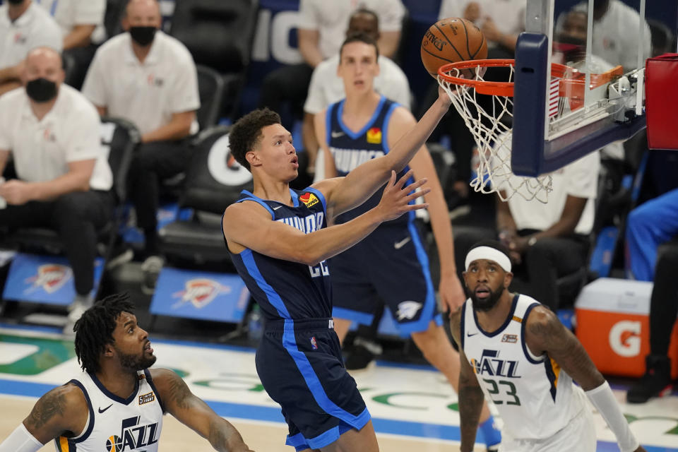 Oklahoma City Thunder center Isaiah Roby, center, shoots between Utah Jazz center Derrick Favors, left, and forward Royce O'Neale (23) in the second half of an NBA basketball game Friday, May 14, 2021, in Oklahoma City. (AP Photo/Sue Ogrocki)