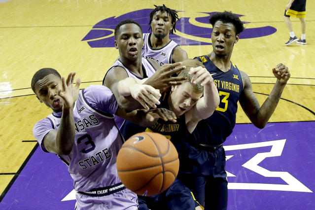 Kansas State's DaJuan Gordon (3) and West Virginia's Sean McNeil battle for a loose ball during the second half of an NCAA college basketball game Saturday, Jan. 18, 2020 in Lawrence, Kan. Kansas State won 84-68. (AP Photo/Charlie Riedel)