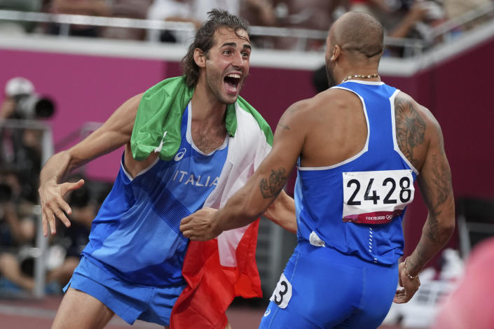High jump gold medalist Gianmarco Tamberi, left, of Italy, congratulates compatriot Lamont Marcell Jacobs, after he won the final of the men's 100-meters at the 2020 Summer Olympics, Sunday, Aug. 1, 2021, in Tokyo. (AP Photo/Matthias Schrader)