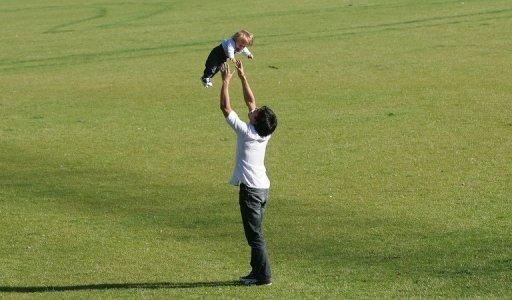 """A young father plays with his child in a park in Berlin. Germany plans to reward parents who look after children at home but opponents say """"Herdpraemie"""", or literally """"oven bonus"""", is out-dated.Concerned by its rapidly ageing population, Germany has been trying since 2005 to lift its low birth rate with paid parental leave in a child's first year and improved childcare facilities"""